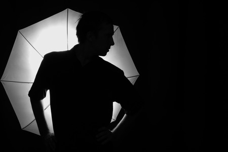 Silhouette of a man on the background of an umbrella flash