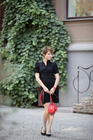 girl with red handbag walking on the street vine-covered