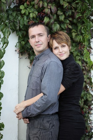 embracing couple standing against a wall with ivy