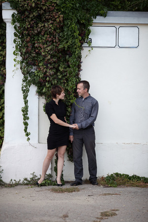 couple standing hand in hand against the wall, ivy-covered