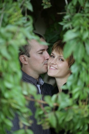 couple kissing in a frame of ivy leaves