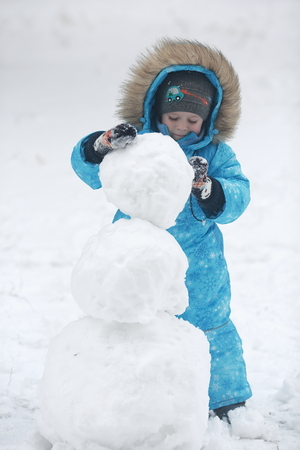 4 year old: 4 year old boy in blue overalls sculpts snowman