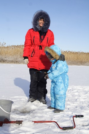 4 year old: 4 year old boy on winter fishing with mom Stock Photo