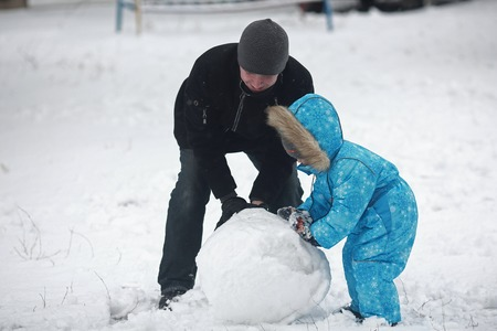 4 year old: 4 year old boy in blue overalls sculpts snowman with his father Stock Photo