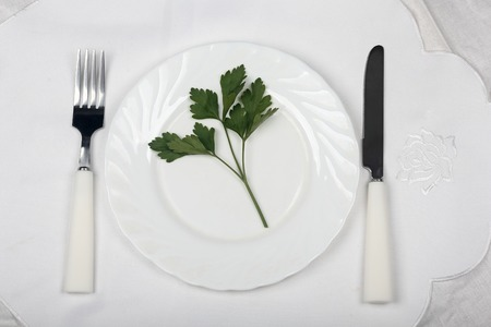 leaf parsley on a plate with knife and fork, symbolizing diet