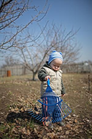 little boy working rake in the garden