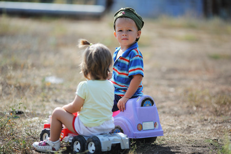 boy and girl riding on toy cars