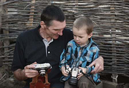 grandfather teaches his grandson to work with the camera Stock Photo