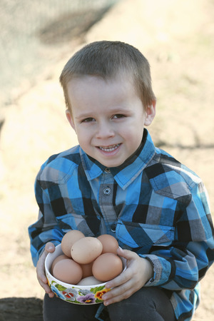 boy holding a cup of chicken eggs