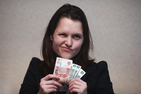 girl looks skeptically at the wad of bills Stock Photo
