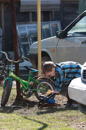 little boy inflates tire with his bike Stock Photo