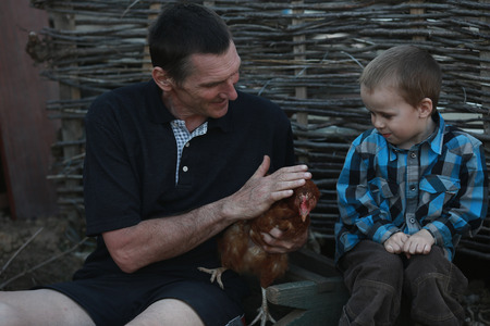 grandfather to his grandson shows colorful chicken