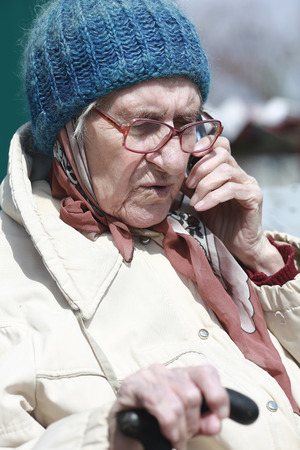old woman with glasses talking on cell phone