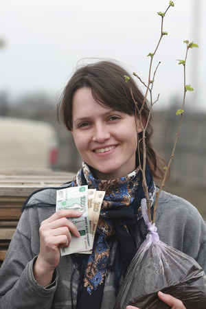 smiling girl holding a tree seedling and banknotes Stock Photo