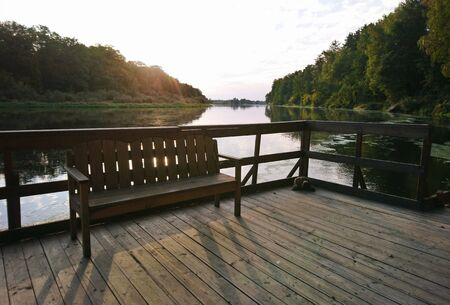 Wooden pier with bench in calm water with reflection of trees on river background. Forest lake in autumn noon