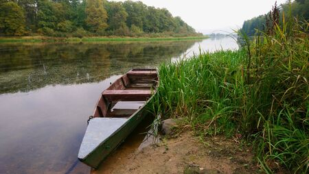 Old wooden rowing boat green on the river amid stunning nature and deciduous forest in foggy autumn weather