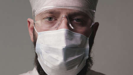 Portrait of a tired middle-aged doctor with a mask on his beard, wearing personal protective equipment on a gray background. Concept of the pandemic. Banque d'images