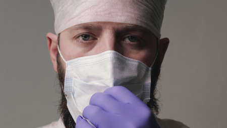 Portrait of middle-aged doctor with mustache and beard, wearing mask and glasses before starting shift in the hospital. Man in protective gear is preparing to meet patients. Concept of health
