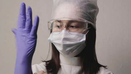 Middle-aged Caucasian female medic in protective gear puts purple rubber glove on her right hand. Training of medical personnel to work in clinic Banque d'images