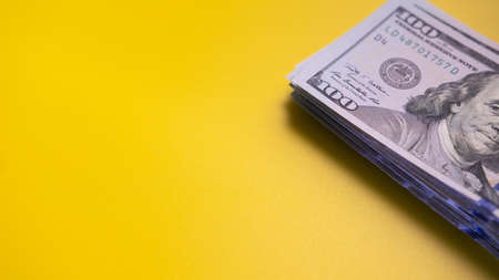 Stack of money with face value of one hundred US dollars on yellow surface. Space for text. Concept of profit and successful investment. Close-up Banque d'images