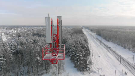 Top of 4G or 5G mobile tower in countryside next to railway on frosty, sunny winter day. Concept of means of communication