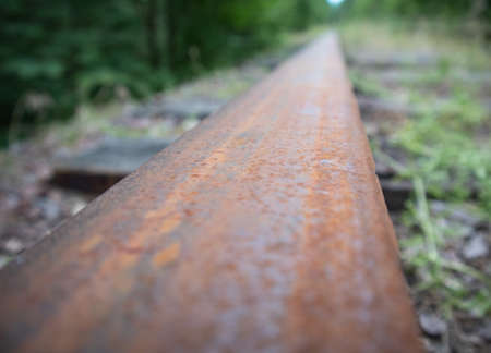 Macro photography of rusty railway rail in rural forest area. Deterioration and obsolescence of infrastructure. Concept of transport crisis