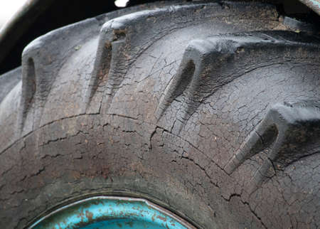 An old tractor tire on dented rim with cracked, worn rubber tread and sidewall. Unacceptable and dangerous operation of agricultural machinery