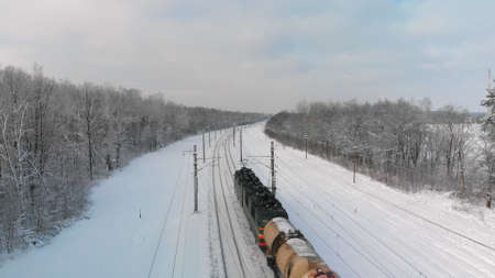 Powerful electric locomotive pulls freight train with various heavy wagons against background of snow-covered winter forest. Aerial view from above Banque d'images