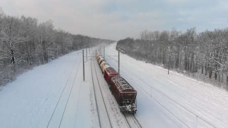 Freight train is moving through a rural wooded area on a frosty day in winter. Concept of trade and transportation. Top view from the back Banque d'images