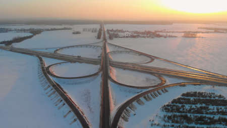 Symmetrical cloverleaf road junction of a highway in winter in a rural area birds-eye view. Type of object in the form of butterfly