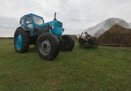 Grey rain clouds over a vintage blue tractor in the countryside against the background of farmland and haystacks. . Unprofitable agribusiness Banque d'images