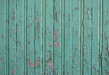 Old wooden background with cracked green paint. Texture of vertical parallel clapboard boards