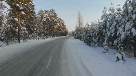 Snow-covered road in a picturesque forest area in the evening. Wide-angle shot Banque d'images