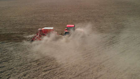 Side view of modern tractor with a sowing unit that sows grain crops in brown sod-podzolic soil. Agricultural machinery raises dust, compacts the soil. Problem of erosion