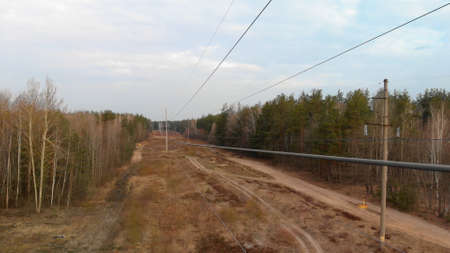 Wide-angle flight close near the power line wires in the forest area. Concept of communication and electrification of remote regions