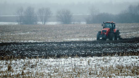 Tractor untimely plows snow-covered farmland in the spring. Risky farming in adverse weather conditions