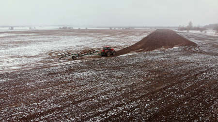 Tractor untimely processes farmland in the spring in a snowfall. Risky farming in adverse weather conditions. Wide-angle view