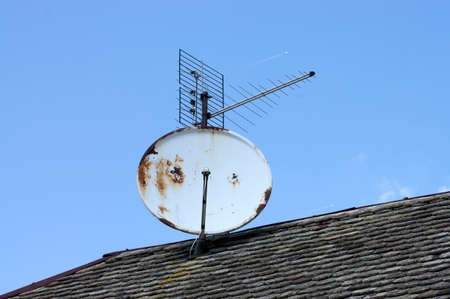 Antenna system on the old roof. At the age of the roof indicate moss and rust.The integrity of the roof is provided by metal formwork.In the background of the antenna, jets are seen. Stock Photo
