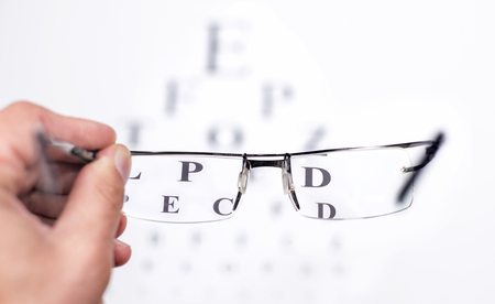 ophthalmic: Looking through glasses at an eye exam chart