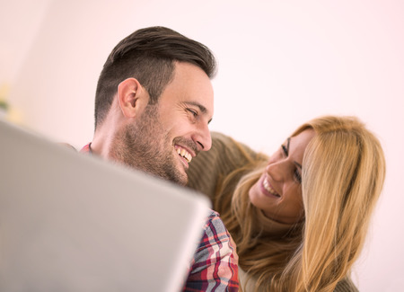 25 30 years: Couple sitting on sofa with laptop.They are sitting close to each other and laughing. Stock Photo