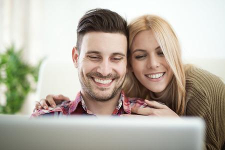 Pares alegres que relaxam junto no sofá surf internet no laptop em home.They está olhando para laptop e sorrindo.