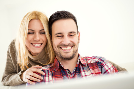 25 30 years women: Young couple browsing internet at home