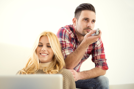 pareja viendo tv: Young couple watching TV at home. Cheerful couple relaxing together on couch surfing internet or watching TV. Foto de archivo