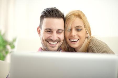 donna innamorata: Coppia giovane navigare in internet a casa, utilizzando il computer portatile e sorridente. Coppie allegre relax insieme a casa.