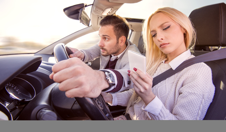25 30 years women: Woman driving a car and typing on a smart phone.