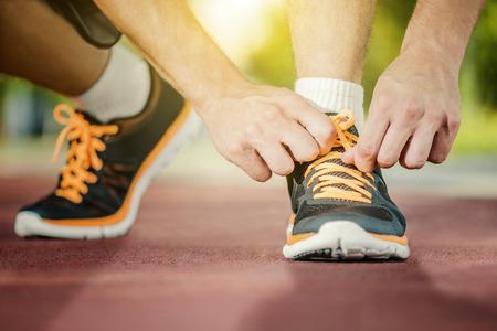 Hombre que ata los zapatos para correr