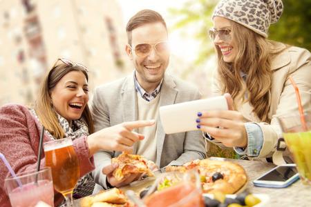 Jonge groep van lachende mensen eten pizza en plezier maken.