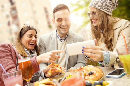 Junge Gruppe Leute lachen, die Pizza essen und Spaß haben.