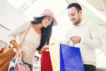 caucasian: Happy young couple with shopping bags.