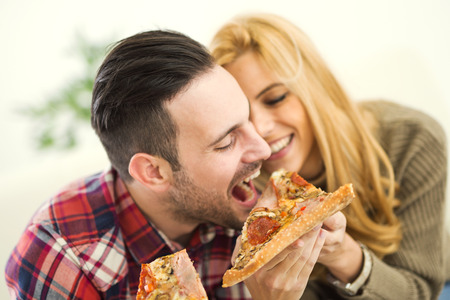 woman only: Portrait of an happy couple.They are laughing and eating pizza and having a great time. Stock Photo